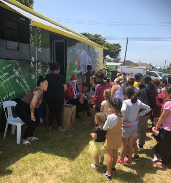 mobile library bus with children waiting outside