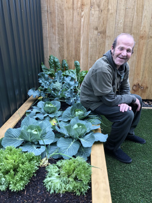 Man sitting on a vegetable garden box